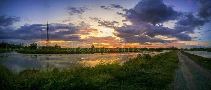 Panorama der Teich reflektiert das Licht von der orange Sonne Der Poolrand ist grünes und gelbes Gras Der Glättungshimmel vor stockfoto