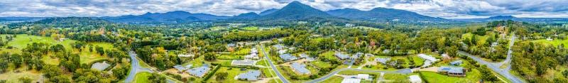 Panorama des maisons entourées par la forêt et les montagnes images stock