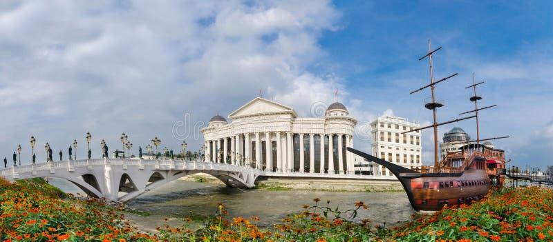 Panorama di giorno di Skopje con il museo archeologico, il ponte dell'occhio ed il ristorante della barca di Galija fotografia stock libera da diritti