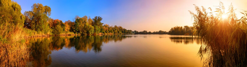 Panorama di tramonto del lago in oro ed in blu fotografia stock
