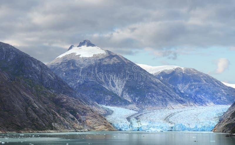Panorama di un ghiacciaio d'Alasca e delle montagne circostanti come incontra il mare immagine stock