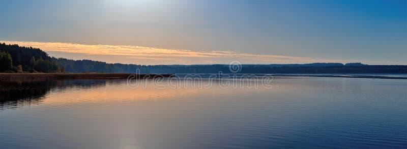Panorama di un tramonto magnifico sul lago, con un colore Dorato-blu immagine stock