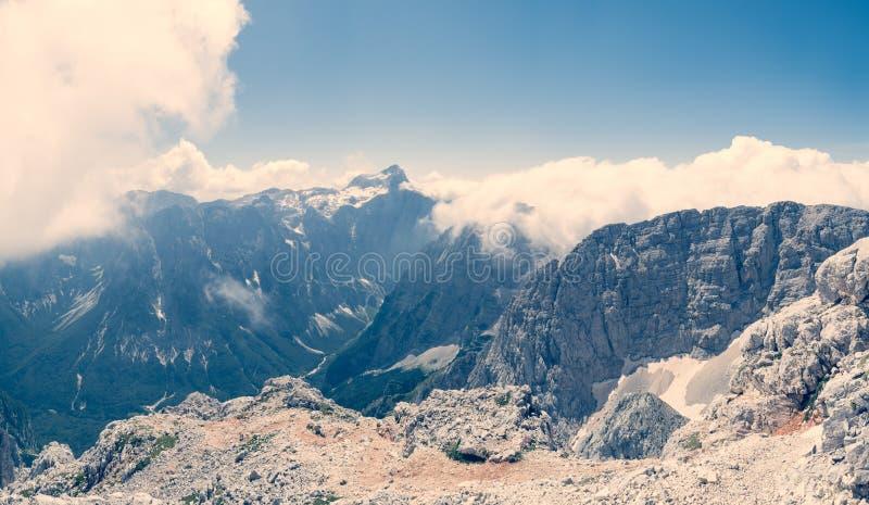 Panorama di una valle della montagna coperta parzialmente di nuvole immagini stock