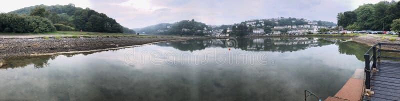 Panorama die over een rivier Van Cornwall naar de plattelandshuisjes van een visserijdorp o kijken royalty-vrije stock foto