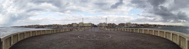 Panorama die van de pier aan de stad met toneeldiehemel kijken door wolken klaar voor de regen wordt behandeld royalty-vrije stock foto's