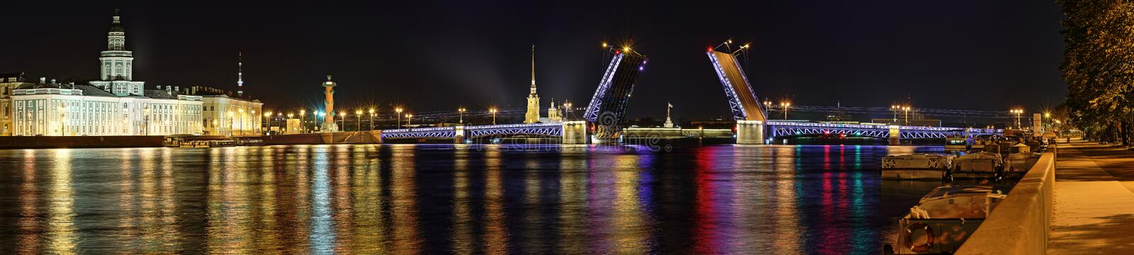 Panorama of the divorced Palace bridge in St. Petersburg. Night wide angle view of divorced Palace bridge, Peter and Paul fortress, the Kunstkamera and Rostral royalty free stock image