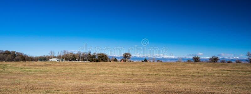 Panorama do campo em Colorado ocidental com explorações agrícolas e da neve tampada fotografia de stock royalty free
