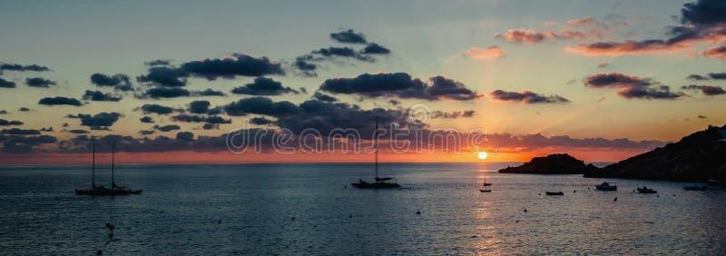 Panorama do por do sol acima do mar Mediterrâneo e da silhueta dos veleiros Ibiza, Spain imagem de stock