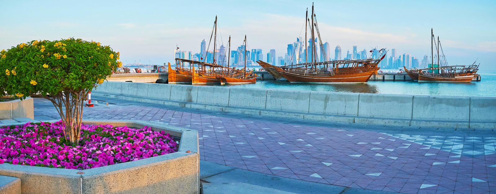 Panorama of Doha harbor, Qatar. Morning is the best time for the lazy walk in Doha harbor, enjoying the beautiful flower beds, old wooden dhow boats and the royalty free stock photography