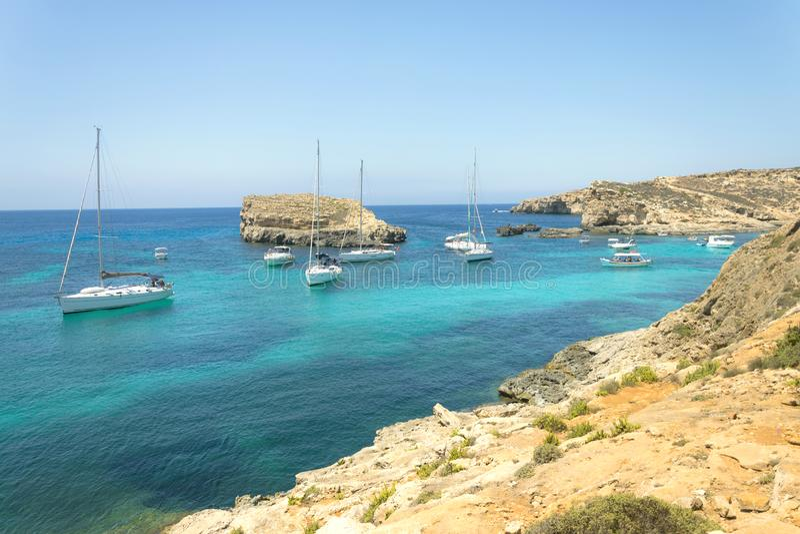 Panorama dos barcos de navigação ancorados no mar aberto na lagoa azul da baía popular na ilha Malta de Comino Azuis celestes aoc foto de stock