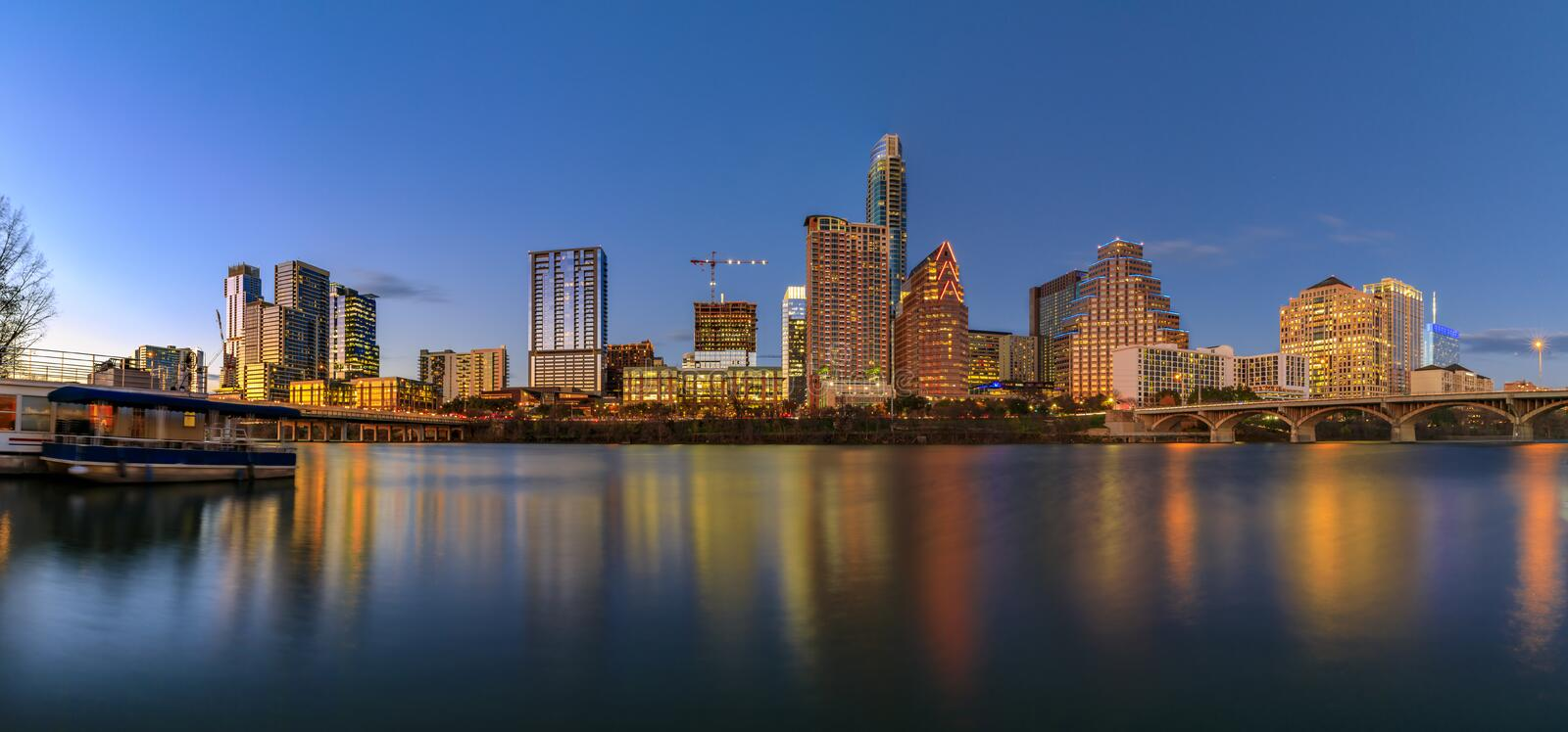 Panorama with downtown view across Lady Bird Lake or Town Lake on Colorado River at sunset golden hour, Austin Texas USA. Panorama with downtown high-rises royalty free stock images