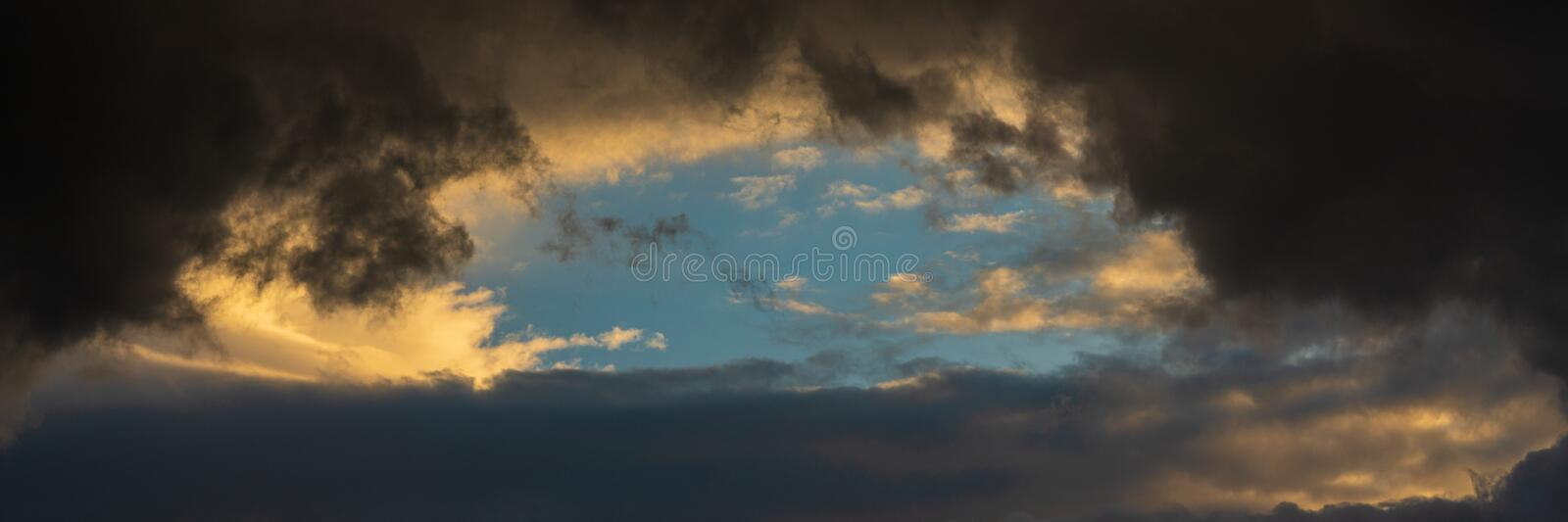 Panorama dramatic clouds illuminated rising of sun floating in blue sky. Natural weather, meteorology background royalty free stock photos