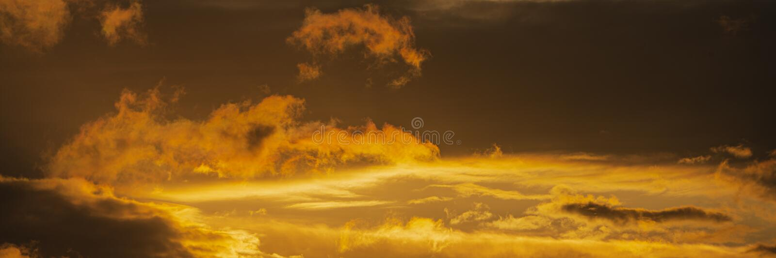 Panorama dramatic clouds illuminated rising of sun floating in sky to change weather. Soft focus, blurred motion royalty free stock image
