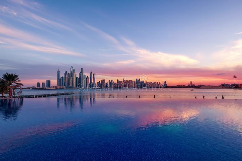 Panorama of Dubai Marina at sunset with a swimming pool in front royalty free stock photo