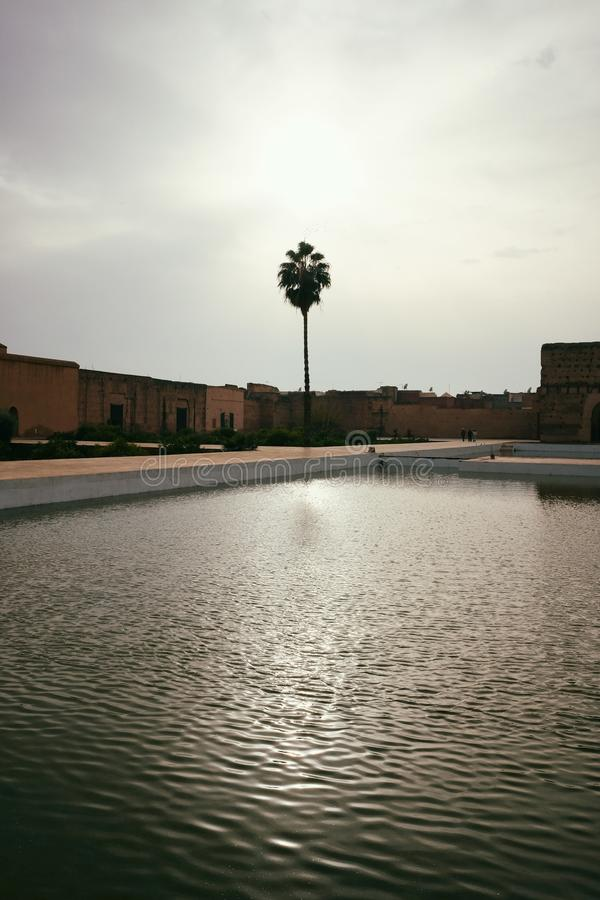 Reflection of El Badi royal palace in the pond. Panorama of El Badi royal palace in Marrakech, Morocco. Popular tourist attraction. View of the pond in the royalty free stock images