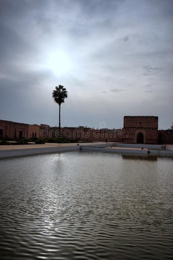 Reflection of El Badi royal palace in the pond. Panorama of El Badi royal palace in Marrakech, Morocco. Popular tourist attraction. View of the pond in the royalty free stock image