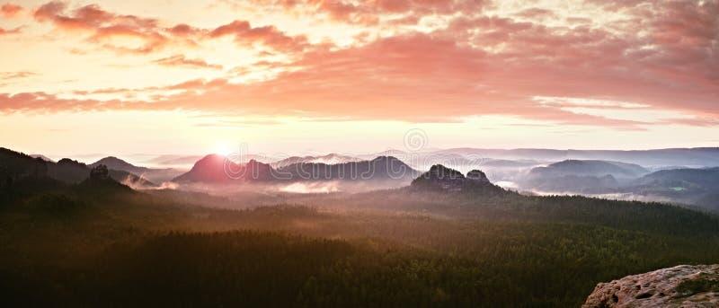 Panorama enevoado vermelho da paisagem nas montanhas Nascer do sol sonhador fantástico em montanhas rochosas Vale enevoado nevoen imagens de stock royalty free