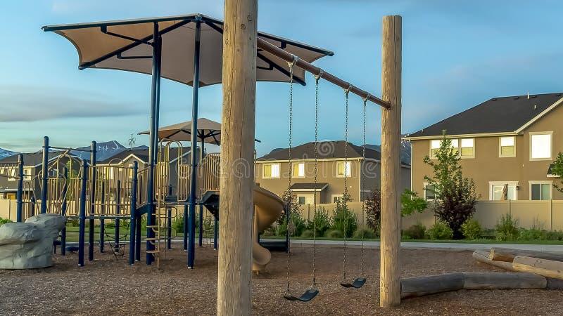Panorama enquadra o playground de vizinhança com slides e balanços contra casas e céu nublado fotos de stock royalty free