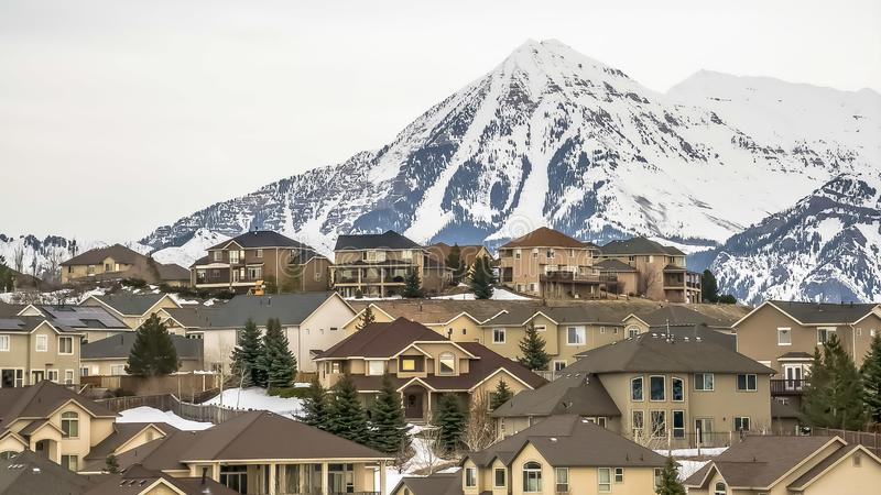 Panorama Exterior view of homes surrounded by fresh white snow and conifers in winter. A towering frosted mountain and cloudy sky can be seen in the background royalty free stock photo