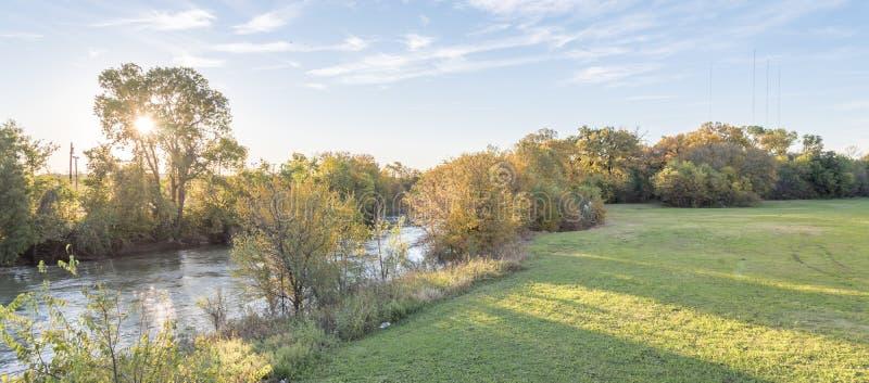 Panorama- färg för nedgånglövverk på flodstranden parkerar och solnedgångmolnet royaltyfria bilder