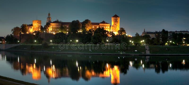Panorama för foto för Krakow Wawel slottnatt på skymning med mörk slyline fotografering för bildbyråer