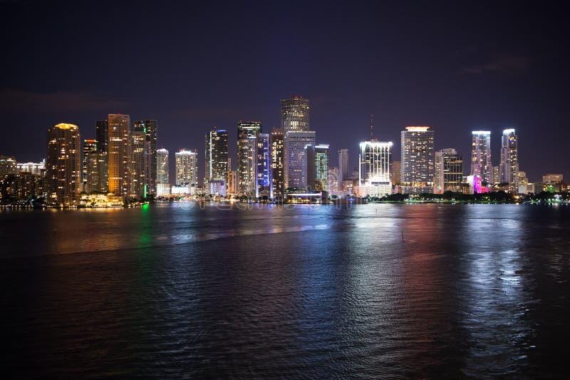 Panorama för Miami stadshorisont på natten, USA Skyskrapabelysning reflekterar på havsvatten i skymning Arkitektur struktur, desi royaltyfri foto