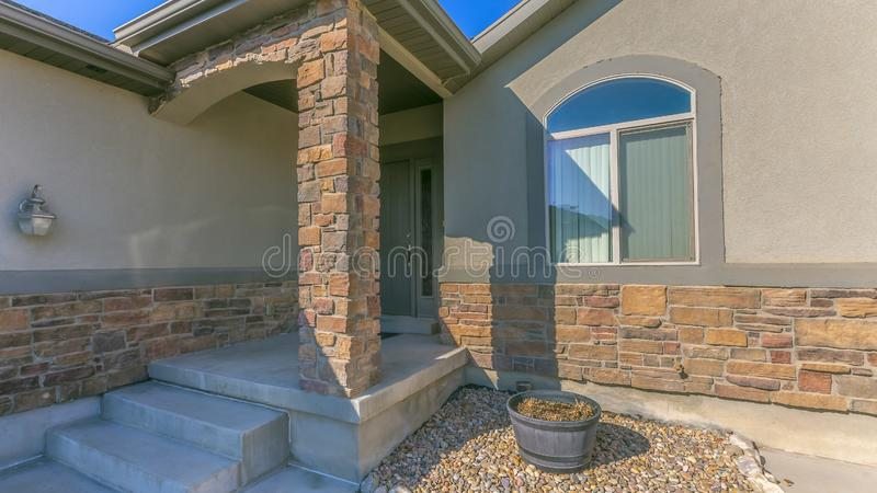 Panorama Facade of a home with a rocky yard and small front porch royalty free stock image