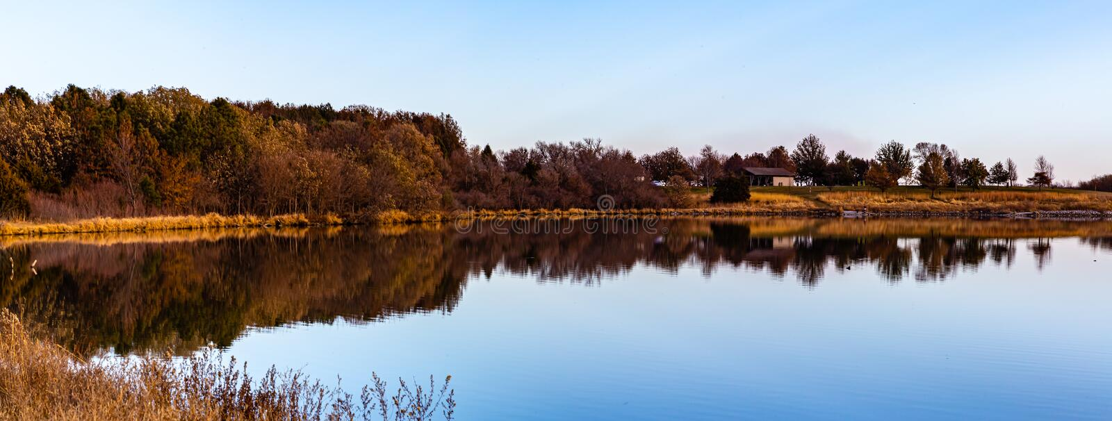 Fall reflections; when the leaves fall, you see a lot more on the shoreline. The tree branches, houses, roads, sheds are visible. Panorama Fall autumn royalty free stock image