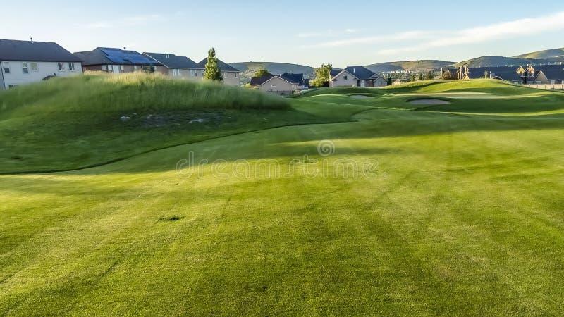 Panorama farwater i bunkiery pole golfowe z w odległości domami i górą fotografia royalty free