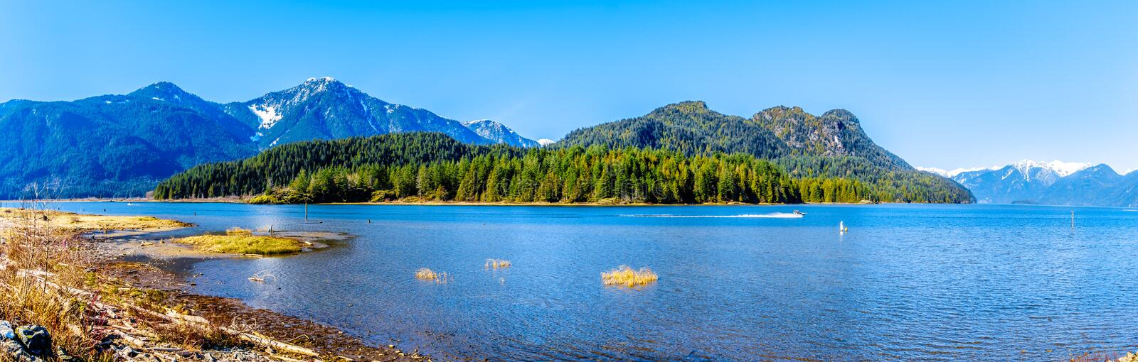 Panorama with a Fishing Boat on Pitt Lake with the Snow Capped Peaks of the Golden Ears and other Mountains in the Coast Mountains royalty free stock images