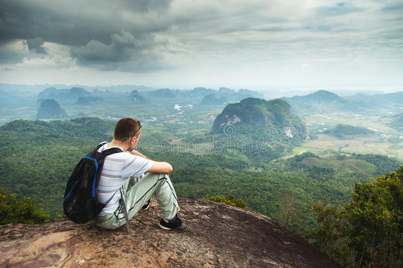 Panorama of fit and active young man resting after hike and enjoying view. Tab Kak Hang Nak Hill Nature Trail. Thailand. royalty free stock photo