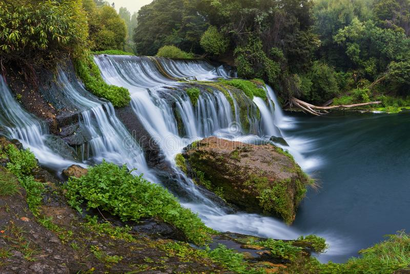 Panorama- fotolandskap/vattenfall som d?ljas i den tropiska djungeln som omges av en naturlig simbass?ng med klar s?tvatten arkivfoton