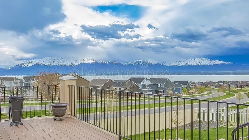 Panorama frame Balcony with wooden floor and metal railing overlooking lake and mountain. Houses along a curving road can also be seen under the striking royalty free stock photography