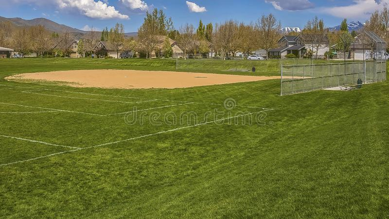 Panorama frame Baseball or softball field with buildings and trees beyond the grassy terrain. The ballpark also has an amazing view of distant mountain and royalty free stock photos