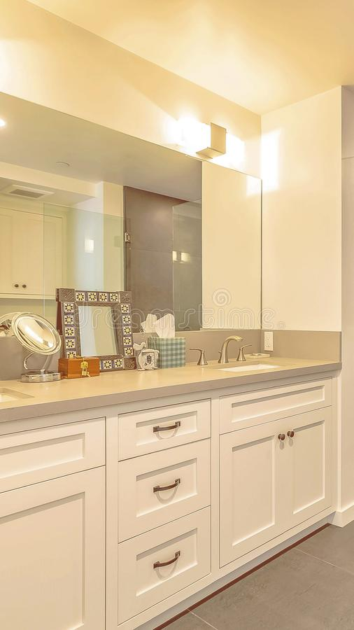Panorama frame Bathroom interior with shower separated from the vanity area by a glass door. The vanity has wood cabinets, double sink, and large mirror royalty free stock photos