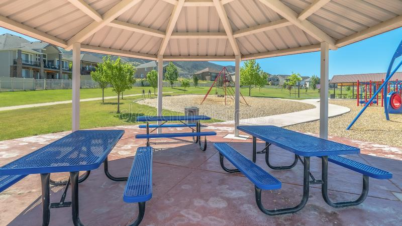 Panorama frame Blue picnic table and seats inside an octagon shape pavilion at a sunny park royalty free stock images