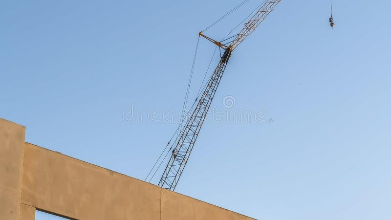 Panorama frame Building under construction with metal crane and blue sky background. The interior metal framework can be seen through the square window holes stock photo
