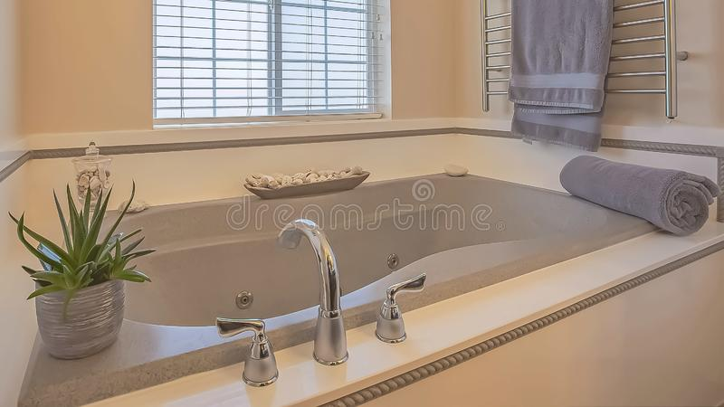 Panorama frame Built in bathtub and wall mounted towel rack inside a bathroom with beige wall. Bathroom ornaments and windows with blinds can also be seen royalty free stock photos
