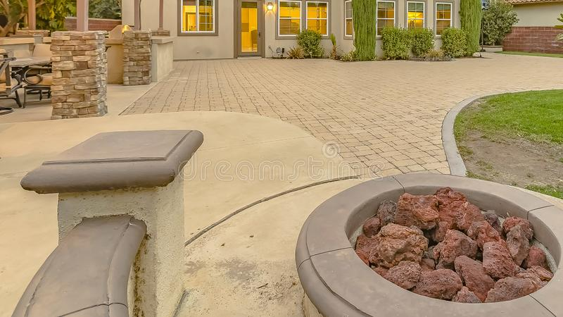 Panorama frame Built in stone bench around a fire pit adjacent to an outdoor dining area. The patio outside the warmly lit house is shaped with concrete and stock photos