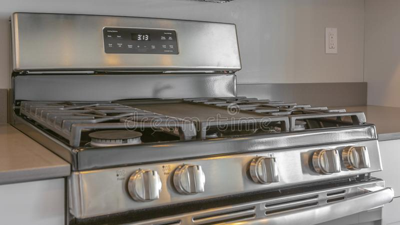 Panorama frame Close up of the cooktop of a range under wall mounted microwave inside a kitchen. The gray wall of this room is lined with built in wooden stock photos