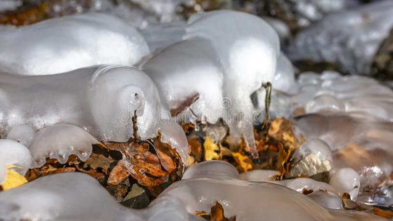 Panorama frame Close up of frozen water on a rocky stream with scattered fallen brown leaves royalty free stock photo