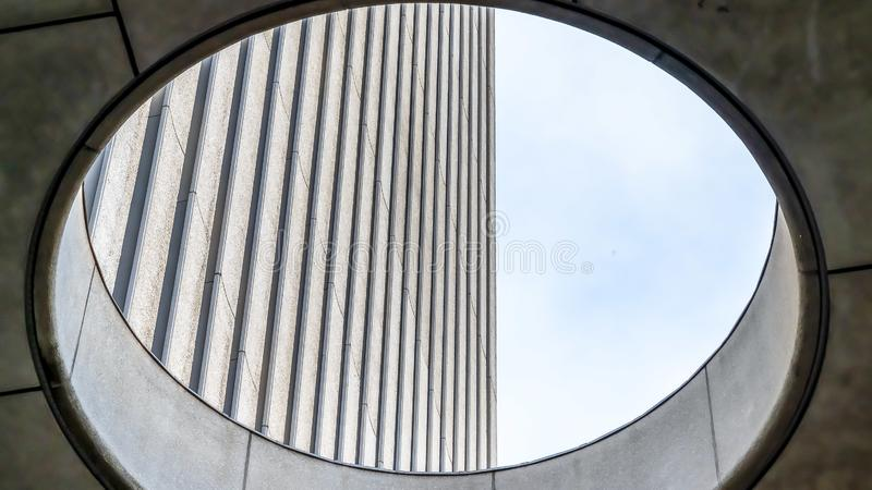 Panorama frame Close up view from the inside of the round skylight of a building. Corrugated concrete wall and bright sky can be seen through the hole stock image