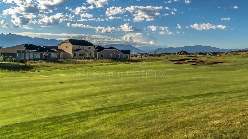 Panorama frame Fairway di un campo da golf in vista di case e montagne sullo sfondo immagine stock libera da diritti