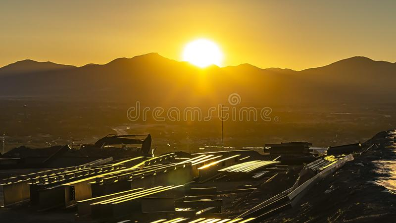 Panorama frame Golden sun behind a silhouetted mountain shining down on the vast valley stock photo