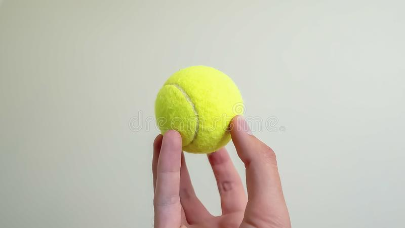 Panorama frame Hand holding a small ball isolated against a shiny white wall background stock image