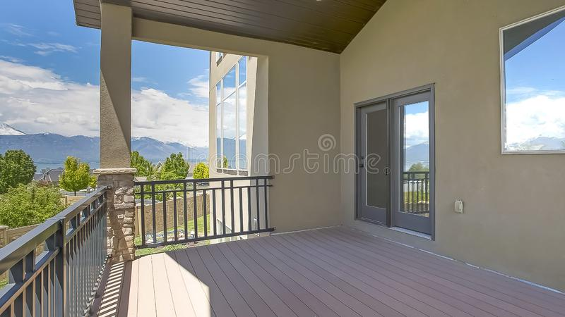 Panorama frame Home with balcony concrete exterior wall and round lights on the wooden ceiling. The cloudy blue sky, lake, and trees are reflected on the glass royalty free stock photos