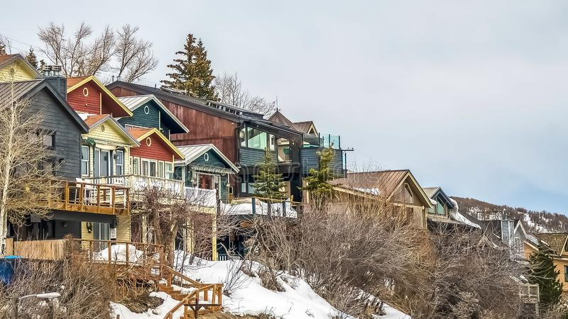 Panorama frame Homes with balconies on a mountain against sky filled with clouds in winter. Outdoor stairs, conifers, and leafless trees cna also be seen on royalty free stock image