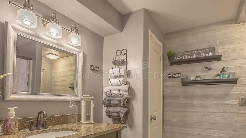 Panorama frame Mirror and lamps above the vanity inside a bathroom with towel rack and shelves. A white curtain conceals the bathtub and shower area royalty free stock images