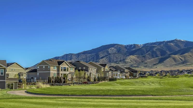 Panorama frame Paved pathway on a vast grassy terrain leading to the houses in the valley. A distant towering mountain can be seen against blue sky on this royalty free stock photography