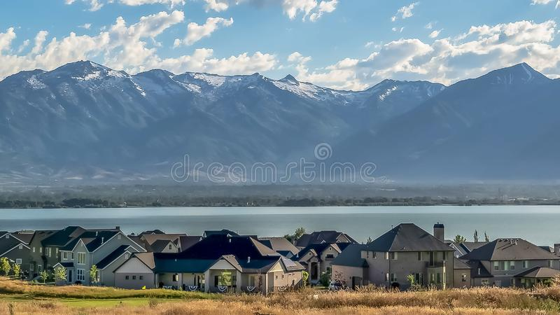 Panorama frame Picturesque landscape with homes overlooking a blue lake and towering mountain royalty free stock image